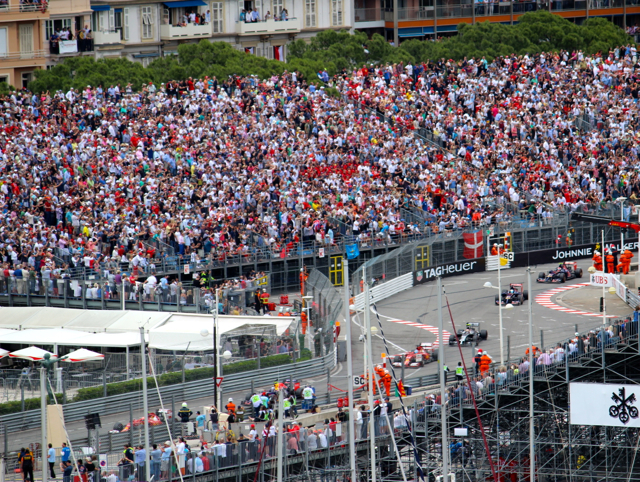Spectators lean forward in the stands to watch the procession of cars.