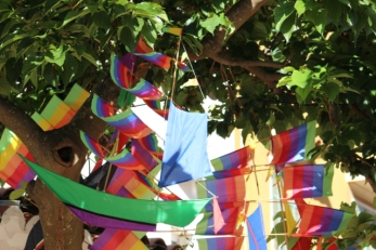 Paper boats hang in the trees outside little eateries