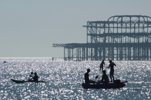Sea farers are silhouetted against the old pier