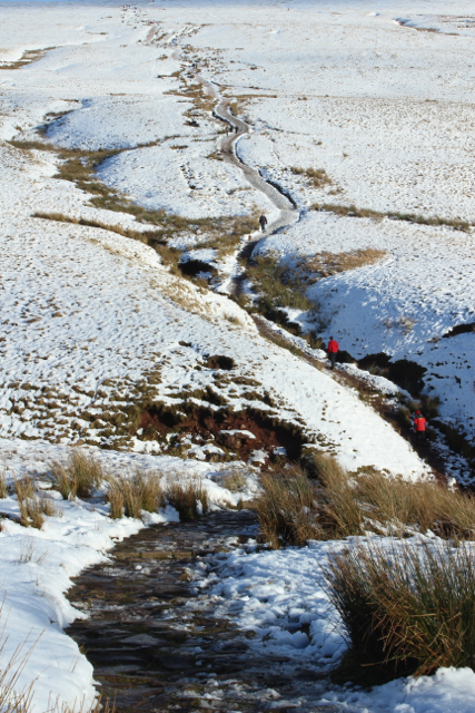 Two hikers negotiate the winding uphills through icy streams and snow covered grasses