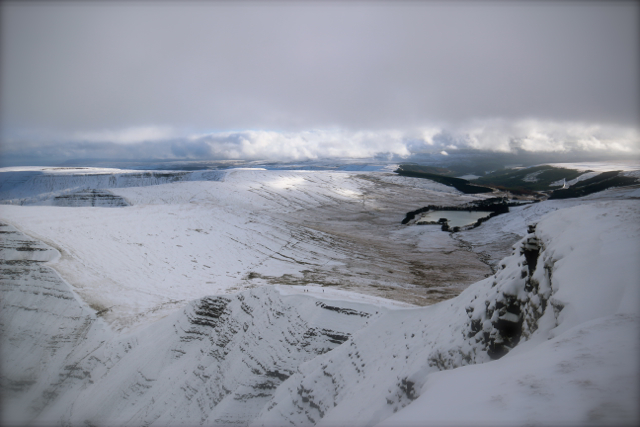Behind the summit, snowy peaks stretch towards a blustery horizon...