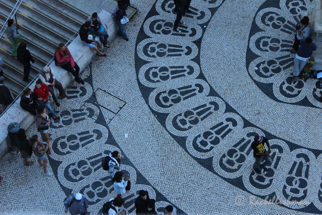 A street dancer entertains passersby on the patterned pavements outside the Baixo Chiado metro station
