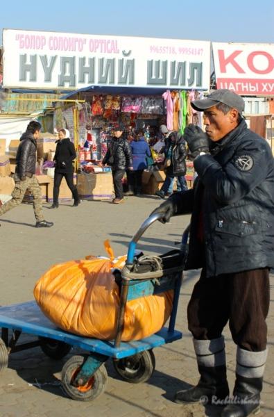 A market trader smokes at the entrance on Ulaanbataar's black market