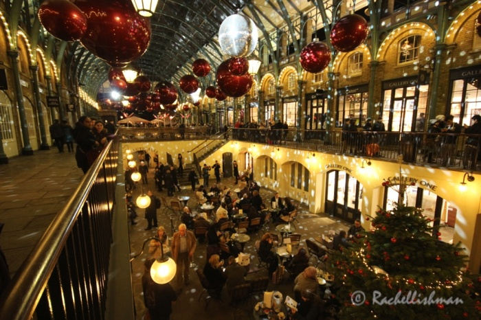 Classical violinists play hymns while people shop and munch in Covent Garden's cafes...