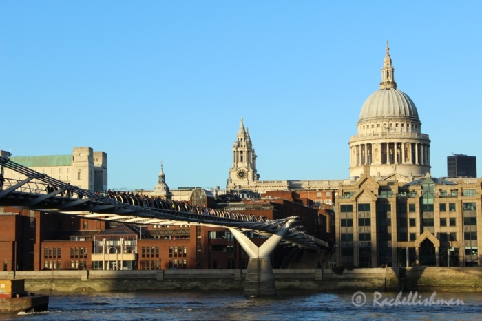Visitors and locals take in some winter sun on Millennium Bridge in front of St Paul's Cathedral