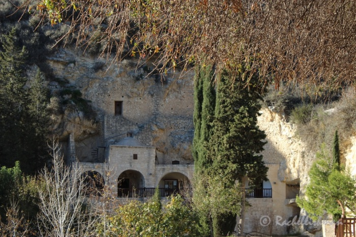 The monastery's original rooms are carved into the rock face beyond a sunny courtyard...