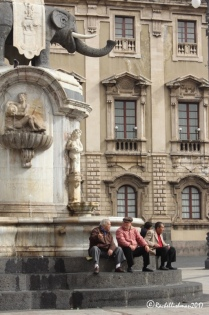 Locals gather underneath Catania's elephant to watch the world go by...