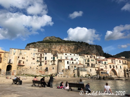 An ancient port with a very cPeople watch people along Cefalu's beach